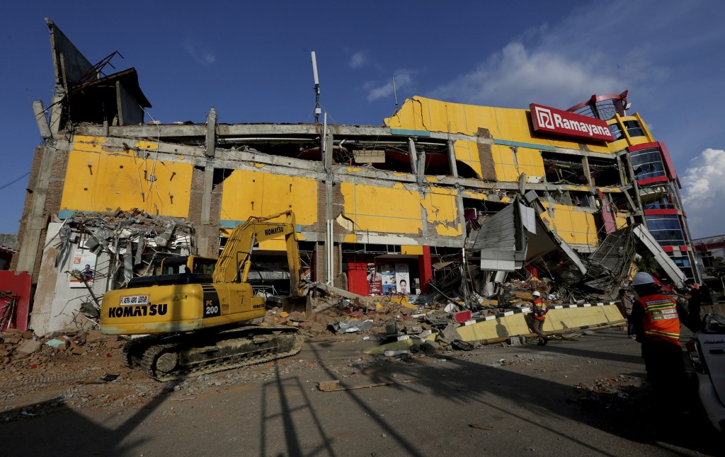An excavator is used to search for victims in the damage Ramayana department store following a massive earthquake and tsunami in Palu, Central Sulawes...