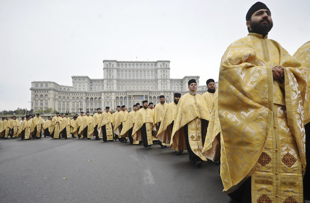 FILE - In this Monday, Oct. 24, 2011, file picture, Romanian orthodox priests walk, backdropped by the communist era built House of the People, curren...