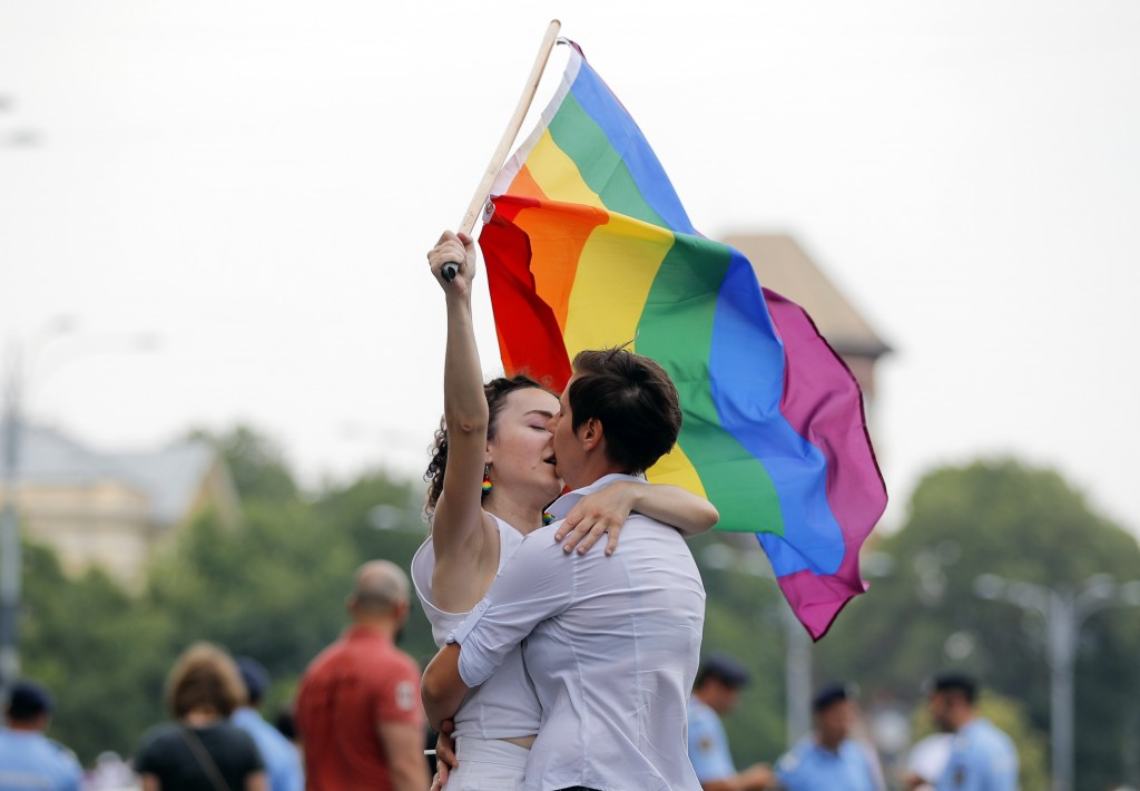 FILE - In this Saturday, June 9, 2018 file photo, two girls kiss holding a rainbow flag during the gay pride parade in Bucharest, Romania. Romania is ...