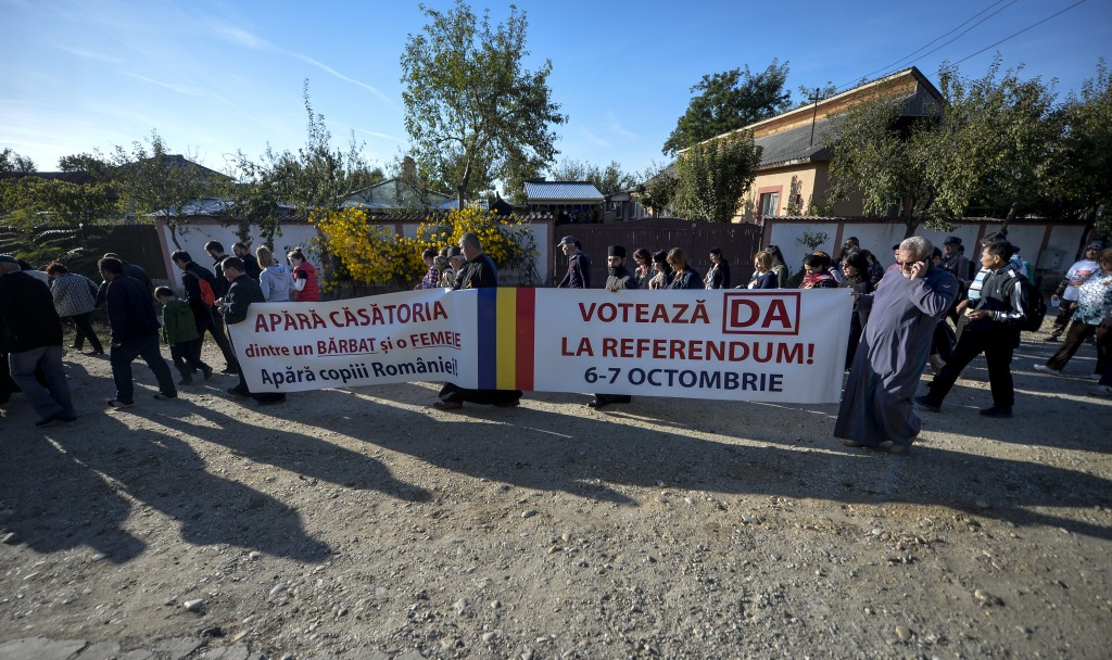"""Priests hold banners that read in Romanian """"Protect Romania's children and the marriage between a man and a woman. Vote Yes!"""" during a rally in suppor..."""