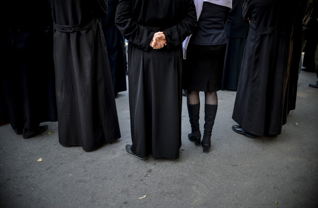 A woman sits between priests during a rally in support of the traditional family, organised by the local church, in the small province town of Dragane...