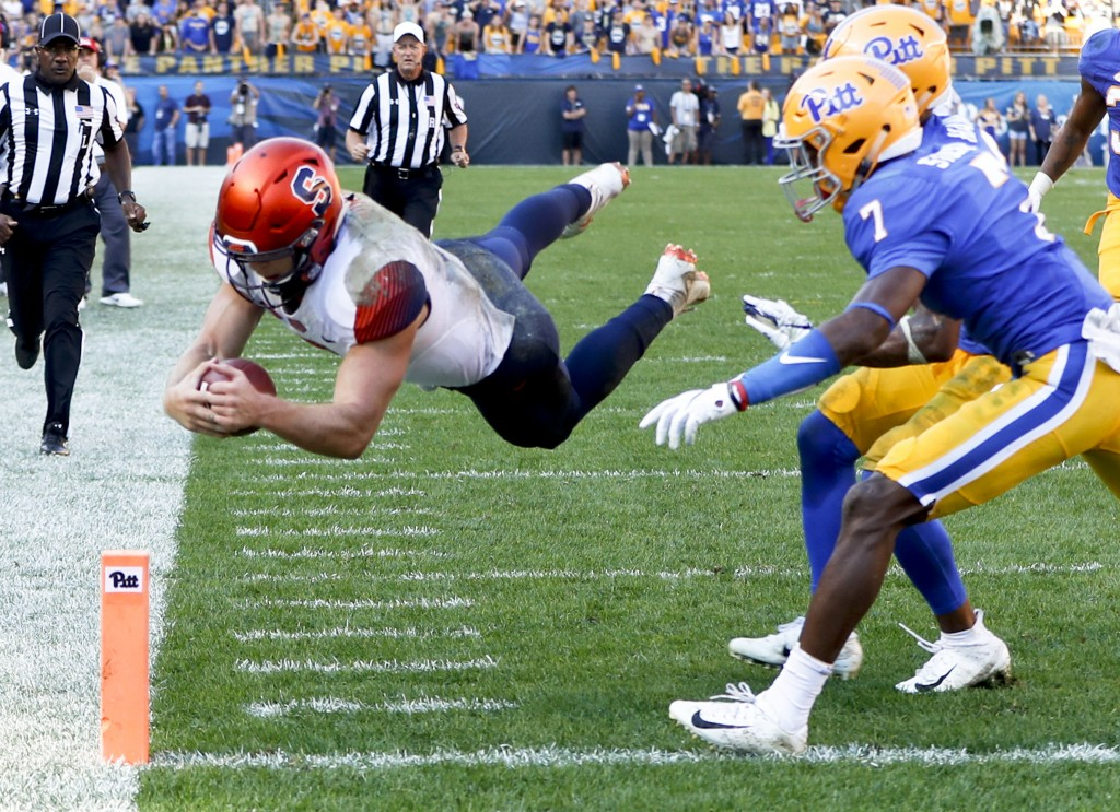 Syracuse quarterback Eric Dungey, left, dives over the goal line Pittsburgh defensive back Jazzee Stocker (7) for a touchdown in the second half of an