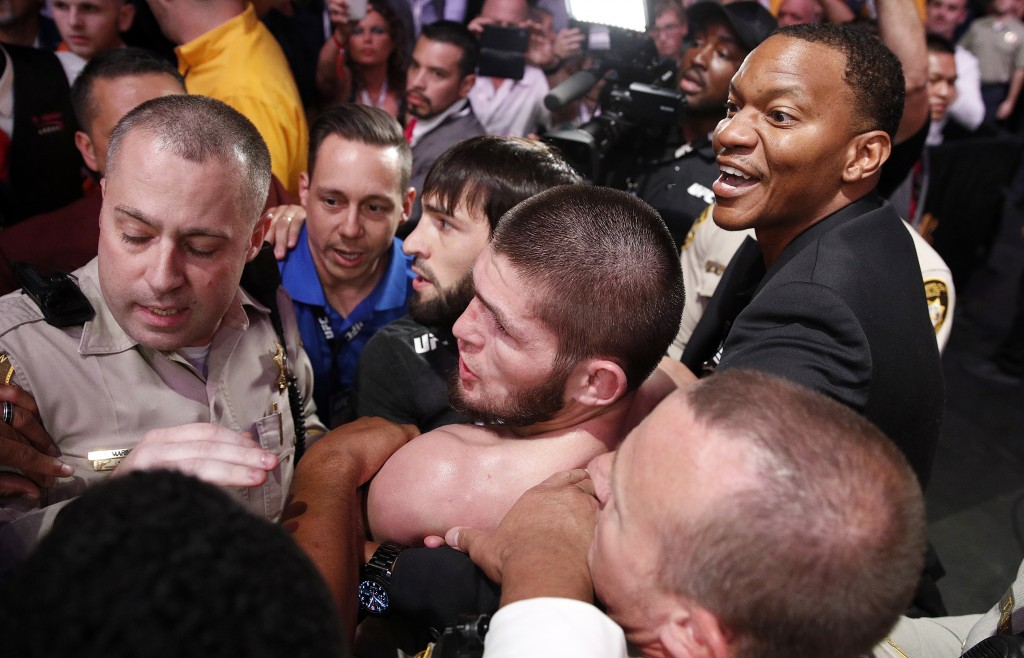 Khabib Nurmagomedov, bottom center, is held back outside of the cage after fighting Conor McGregor in a lightweight title mixed martial arts bout at U