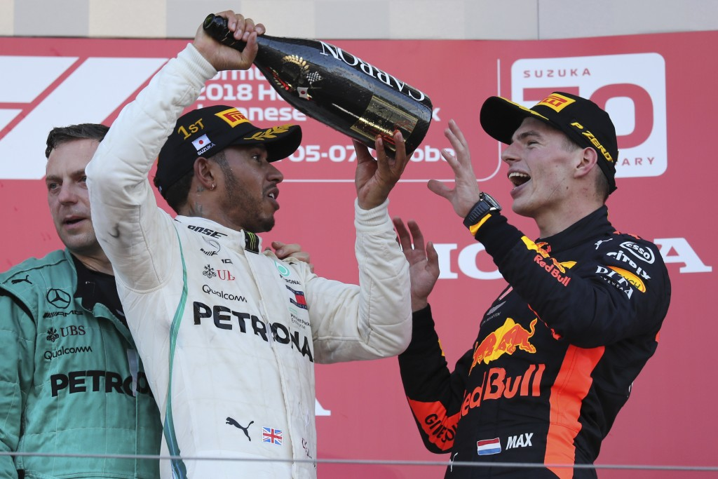 Race winner Mercedes driver Lewis Hamilton prepares to pour champagne on third placed Red Bull Racing driver Max Verstappen, left, as they celebrate o