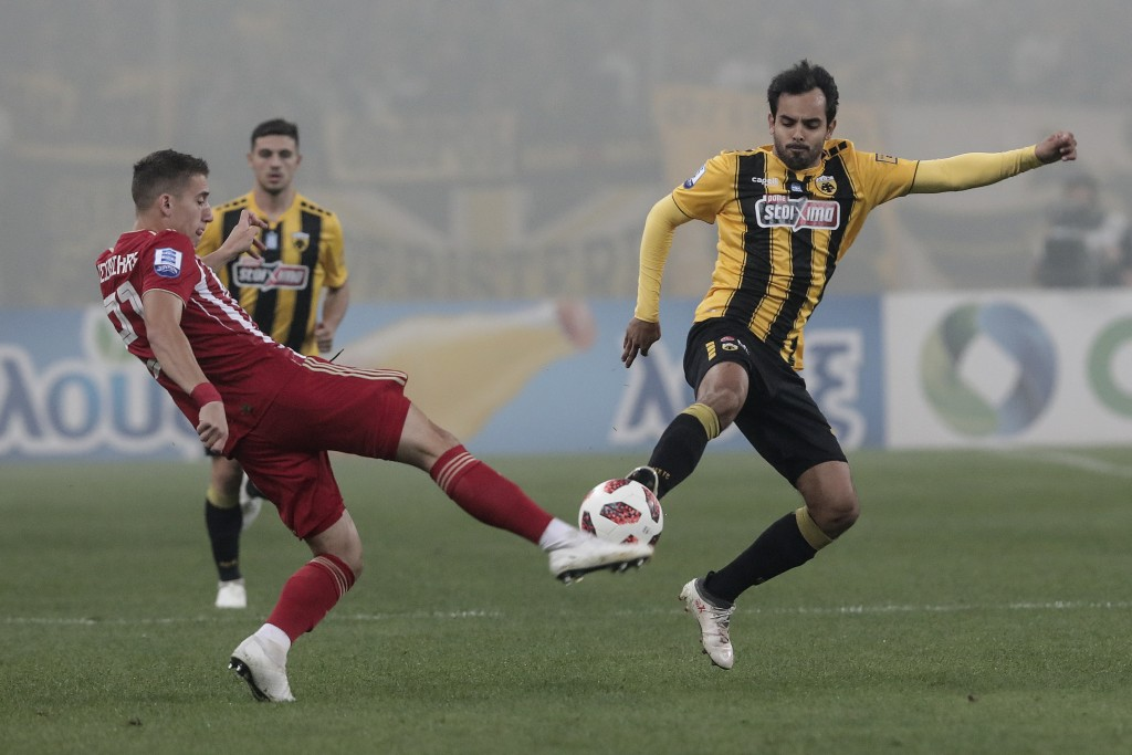 AEK Athens' Rodrigo Galo, right, battles for the ball with Olympiakos' Giannis Masouras during their Greek Super League soccer match at Olympic stadiu