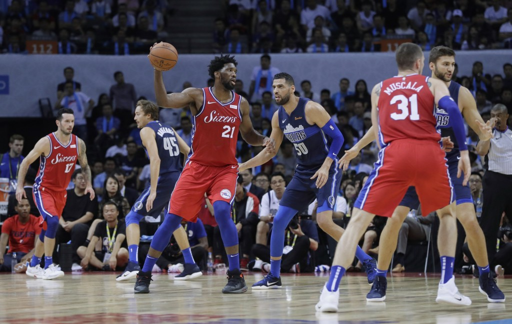Joel Embiod of the Philadelphia 76ers, third left, controls the ball away from Salah Mejri of Dallas Mavericks, third right, during the Shenzhen baske