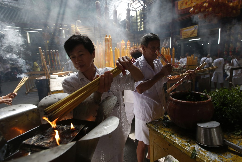 In this Oct. 8, 2018, photo,  a woman lights long incense sticks at a Chinese temple in Bangkok, Thailand, to mark the eve of the Vegetarian Festival.