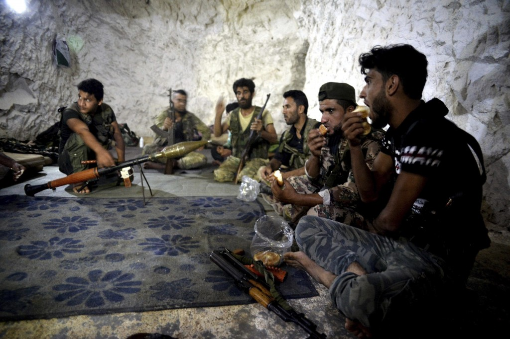 FILE - In this Sunday, Sept. 9, 2018 file photo, fighters with the Free Syrian army eat in a cave where they live, on the outskirts of the northern to
