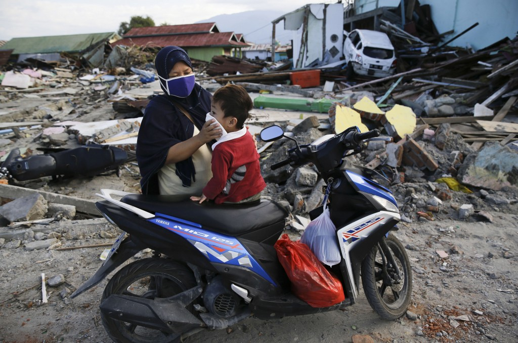 In this Oct. 6, 2018, photo, a woman covers the face of her son as they visit the area where they used to live before a massive earthquake and tsunami...