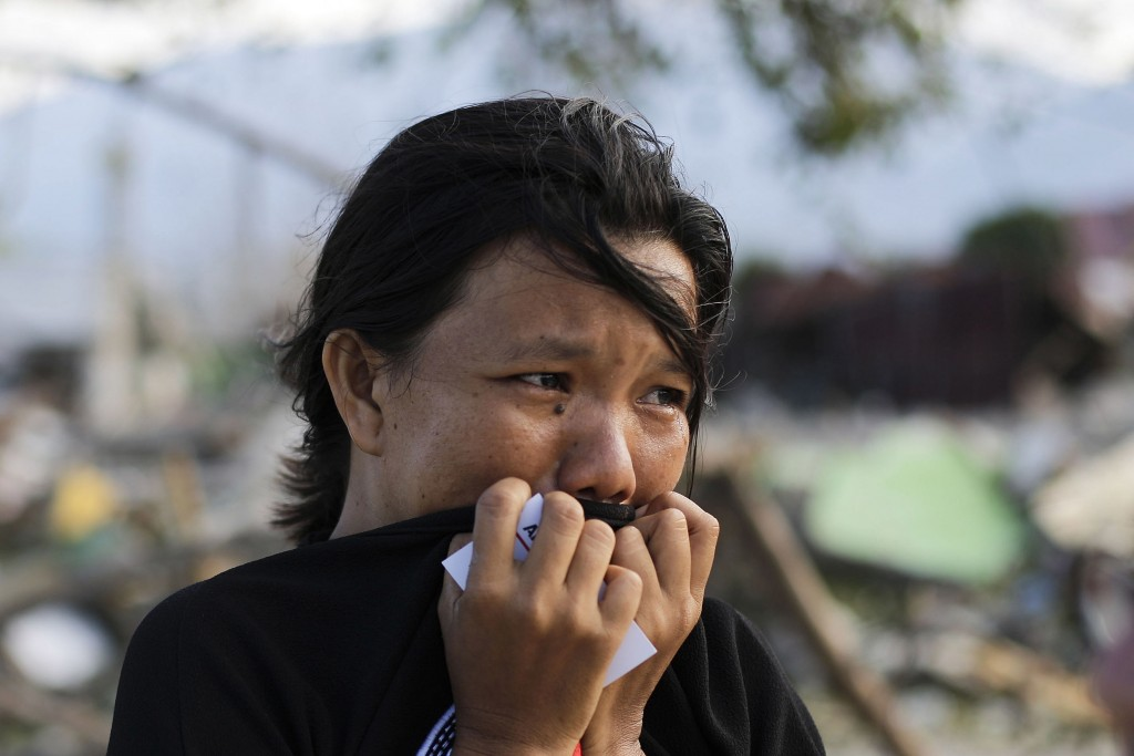 In this Oct. 5, 2018, file photo, Musrifah breaks into tears as she visits the area where her house used to stand before a massive earthquake and tsun...