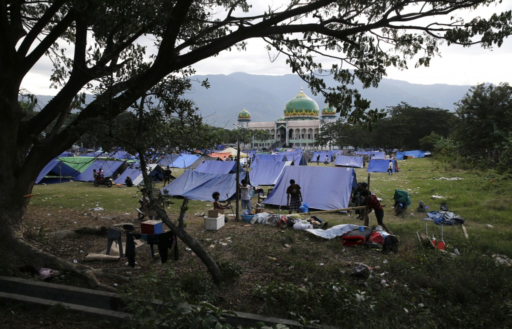 In this Oct. 5, 2018, photo, evacuees pitch tents outside a damaged mosque after their homes were damaged when a massive earthquake hit the Balarola n...