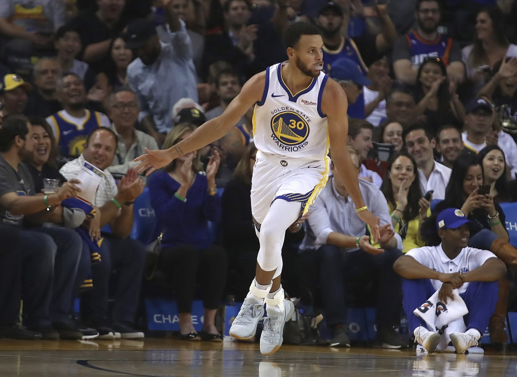 Golden State Warriors' Stephen Curry celebrates after scoring against the Phoenix Suns during the first half of a preseason NBA basketball game Monday