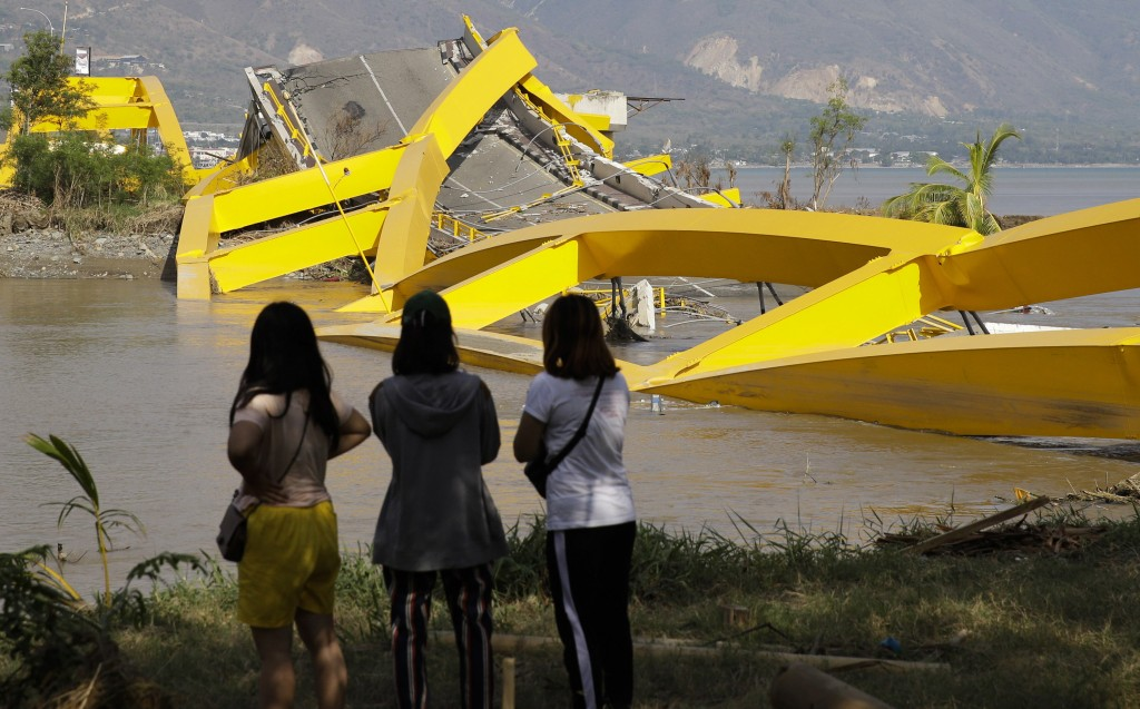 In this Oct. 4, 2018, photo, villagers look at the damage on the city's iconic yellow Teluk Palu Bridge after a massive earthquake and tsunami damaged...