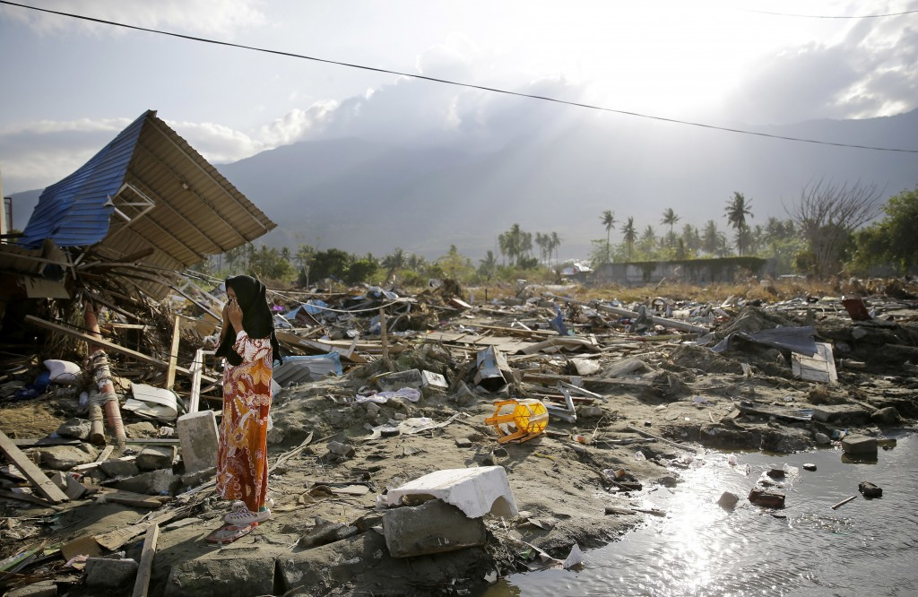 In this Oct. 4, 2018, file photo, a woman walks past toppled structures along a busy road in the earthquake and tsunami-damaged Palu, Central Sulawesi...