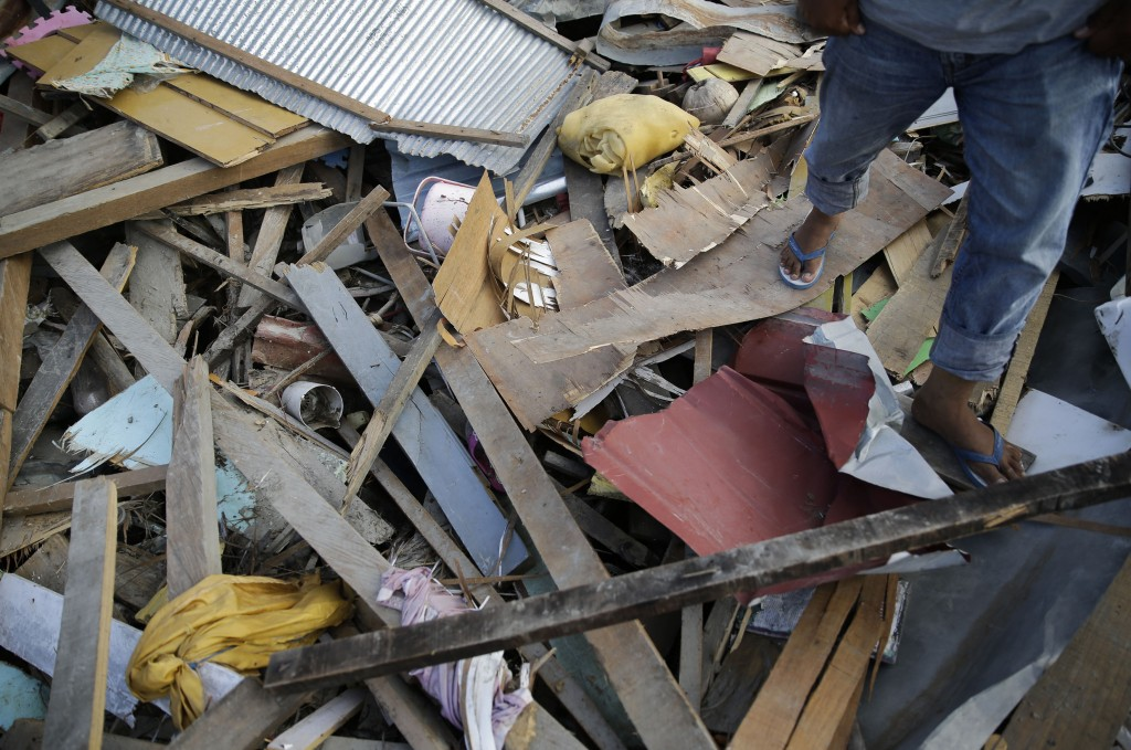 In this Oct. 5, 2018, photo, villagers walk over piles of debris as they search for the missing and any usable items in an area hit by a wall of mud a...
