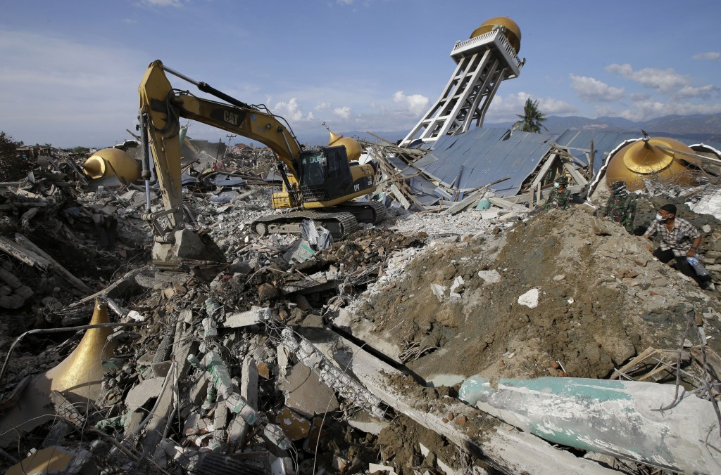 In this Oct. 6, 2018, photo, a backhoe is used during recovery operations beside a toppled mosque in an area hit by liquefaction, the movement of satu...