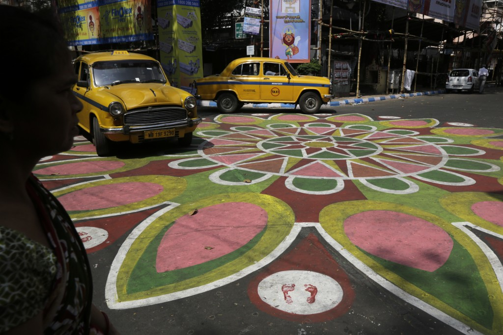 In this Oct. 9, 2018, photo, an Indian woman, left and two yellow cabs prepare to cross an intersection of a street painted with colors ahead of Hindu