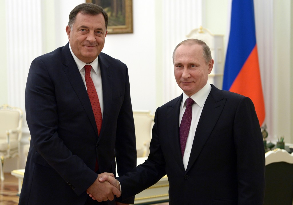 FILE - In this Thursday, Sept. 22, 2016 file photo, Russian President Vladimir Putin, right, shakes hands with President of the Republic of Srpska Mil...