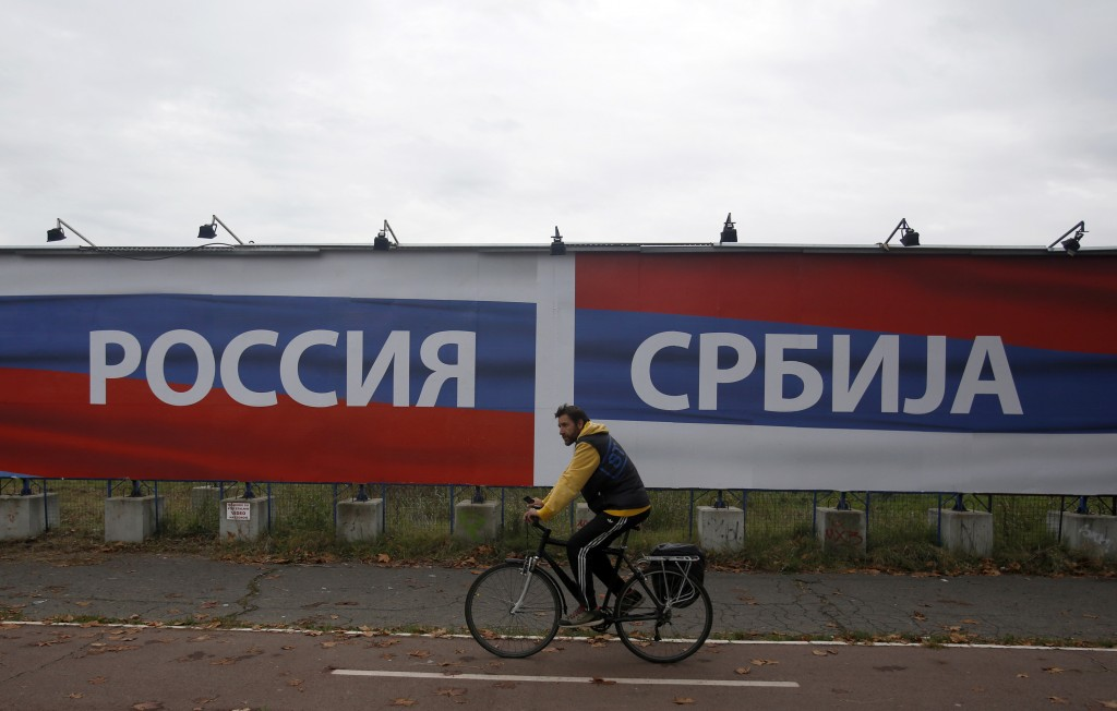FILE - In this Friday, Oct. 17, 2014 file photo, a man rides bicycle pasts a billboards reading 'Russia' , left and 'Serbia', in Belgrade, Serbia. Jus...