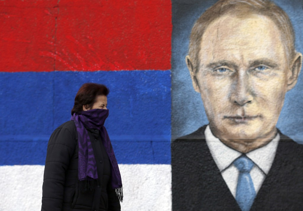 FILE - In this Tuesday, Dec. 6, 2016 file photo, a woman passes by graffiti depicting the Russian President Vladimir Putin in a suburb of Belgrade, Se...