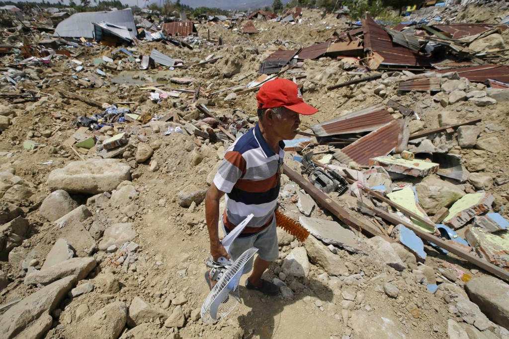 In this Oct. 6, 2018 photo, a man retrieves items from toppled structures in the Balarola neighborhood of Palu city when a massive earthquake caused t...