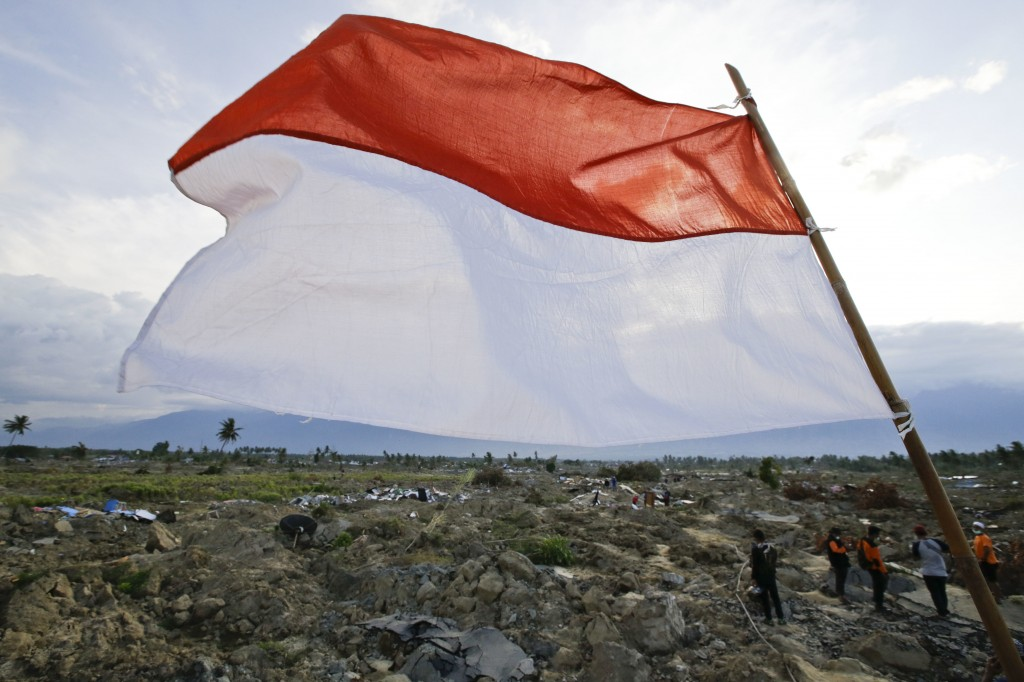 In this Oct. 6, 2018, photo, the national flag flies over the damaged neighborhood of Petobo where houses used to stand in Palu, Central Sulawesi, Ind...