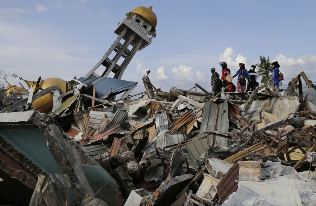 In this Oct. 6, 2018, photo, villagers wait for any word on their missing relatives lost in the Balarola neighborhood of Palu city when a massive eart...