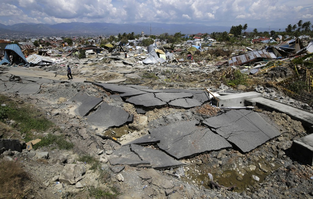 In this Oct. 6, 2018, photo, an asphalt road and toppled houses scatter across an area hit by liquefaction during an earthquake in the Balaroa neighbo...