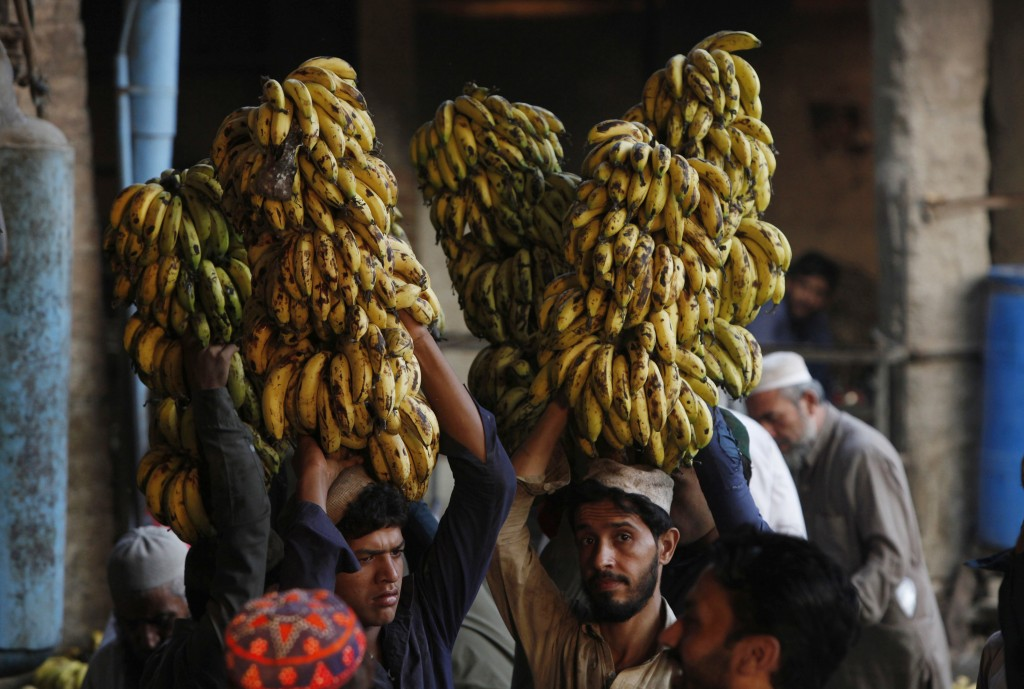 FILE - In this Wednesday, Sept. 12, 2018, file photo, vendors carry banana on their heads at a fruit and vegetable market in Peshawar, Pakistan. Pakis