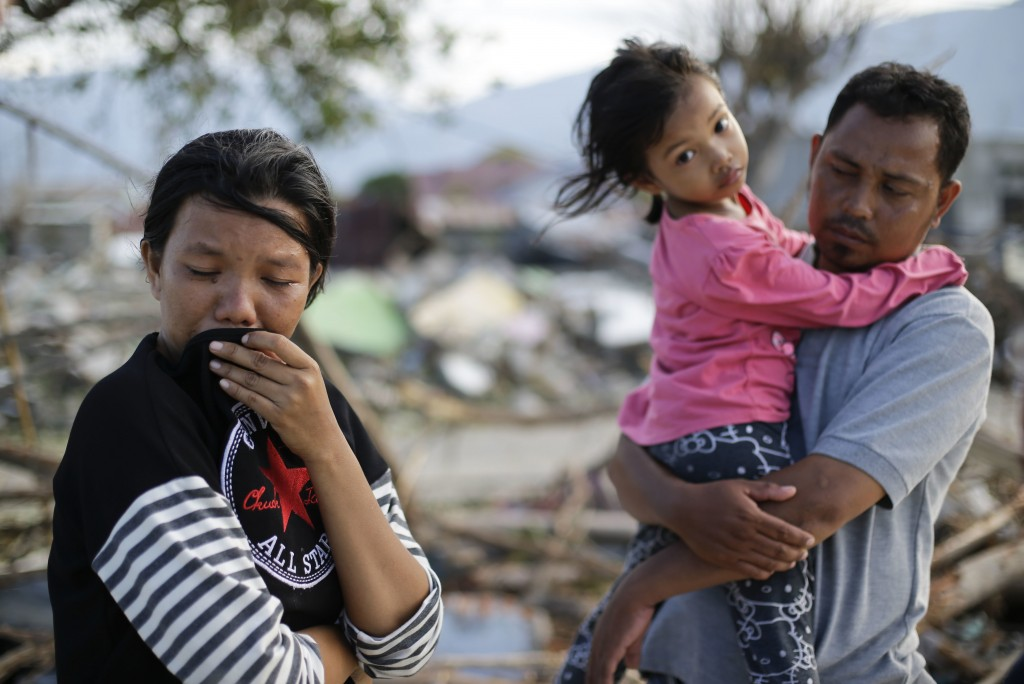 In this Oct. 5, 2018, photo, Musrifah, left, cries beside her husband Hakim and daughter Syafa Ramadi as they visit the area where their house used to...