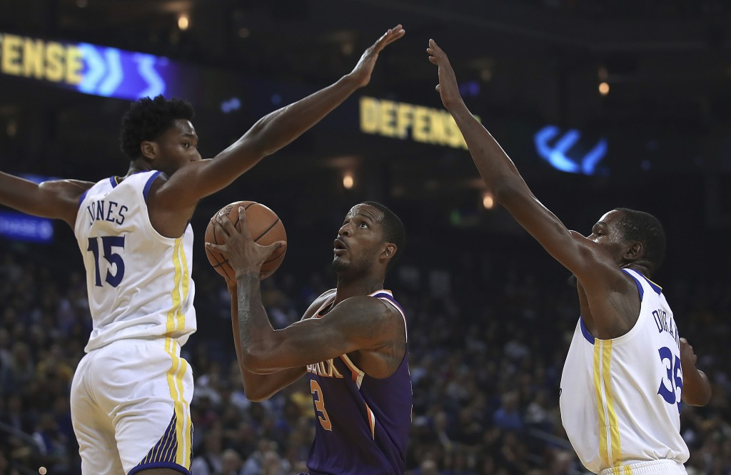 Phoenix Suns' Trevor Ariza, center, looks to shoot between Golden State Warriors' Damian Jones (15) and Kevin Durant, right, during the first half of