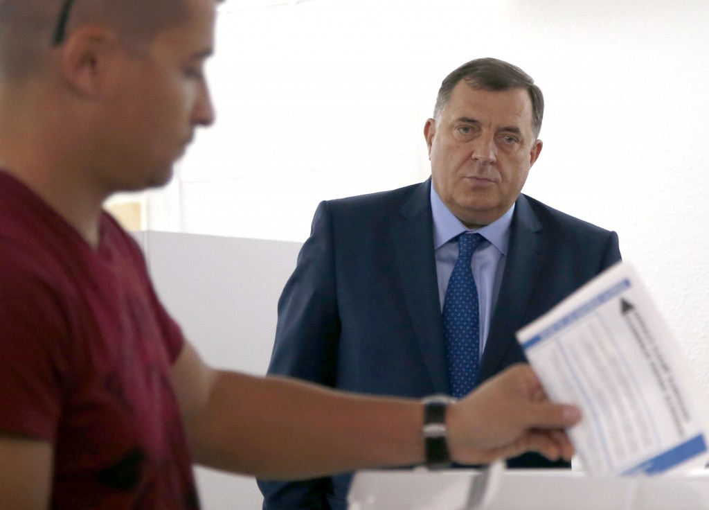 In this photo taken on Sunday, Oct. 7, 2018, President of the Republic of Srpska Milorad Dodik, right, waits at a polling station in the Bosnian town ...