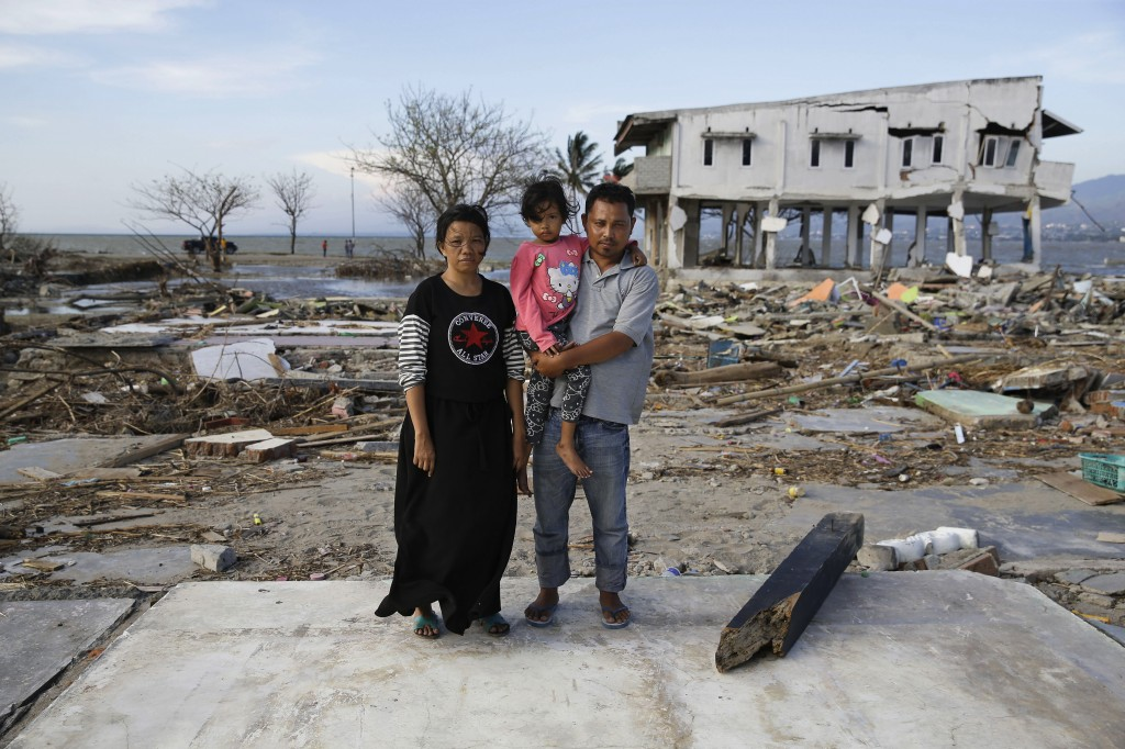 In this Oct. 5, 2018, photo, Musrifah, left, and her husband Hakim, right, and their daughter Syafa Ramadi pose where their house once stood before a ...
