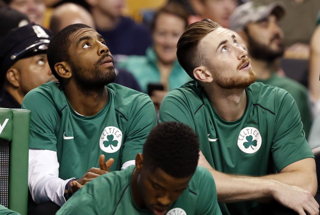 FILE - In this Oct. 9, 2017 file photo Boston Celtics' Kyrie Irving, left, and Gordon Hayward look on from the bench during the first quarter of a pre