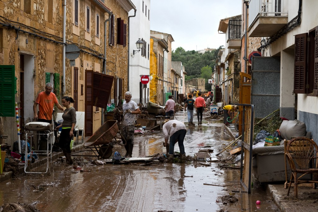 Residents clear mud from a flooded dstreet in Sant Llorenc, 60 kilometers (40 miles) east of Mallorca's capital, Palma, Spain, on Wednesday, Oct. 10,