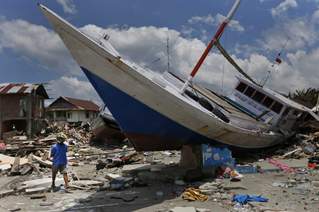 In this Oct. 10, 2018, photo,  a man walks past a boat swept ashore by a tsunami in Wani village on the outskirt of Palu, Central Sulawesi, Indonesia.