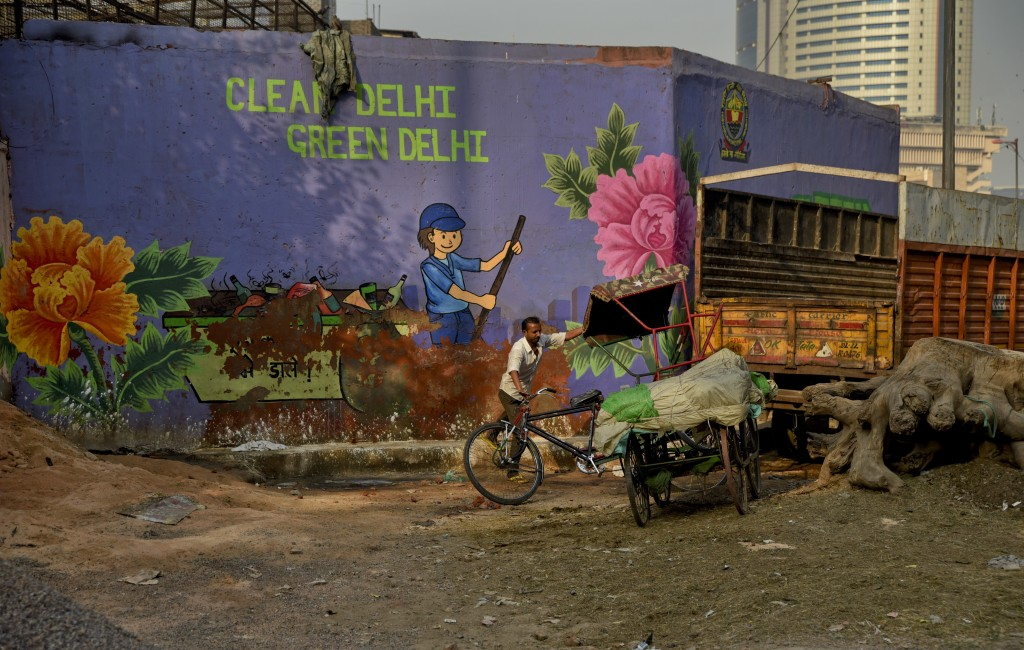 In this Oct. 10, 2018, photo, an Indian cycle rickshaw puller maneuvers his rickshaw past an awareness mural campaigning for a clean and green Delhi i