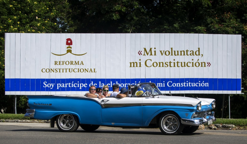 In this Oct. 2, 2018 photo, tourists take a joy ride in a vintage convertible car, past a billboard promoting constitutional reform with the Spanish m