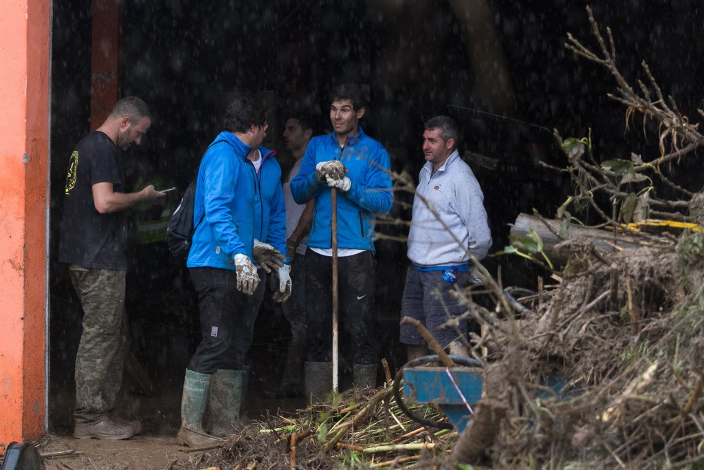 Spanish tennis player Rafael Nadal works with residents to clear the mud from their houses after flooding in Sant Llorenc, 60 kilometers (40 miles) ea