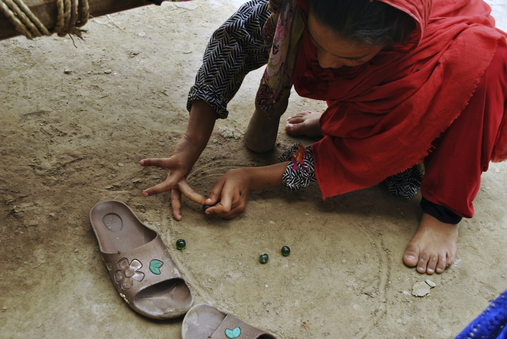 In this Friday, August 10, 2018, photo,  in Mardan, Pakistan, Ansa Khan plays marbles on the dirt floor of her home. This is the most famous game in r