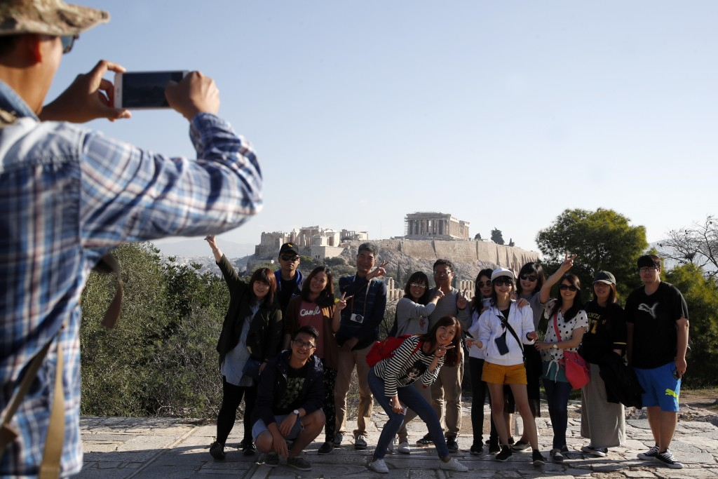 Tourists from Taiwan take photographs with the closed Acropolis ancient site in the background in Athens, Thursday, Oct. 11, 2018 during a 24-hour str