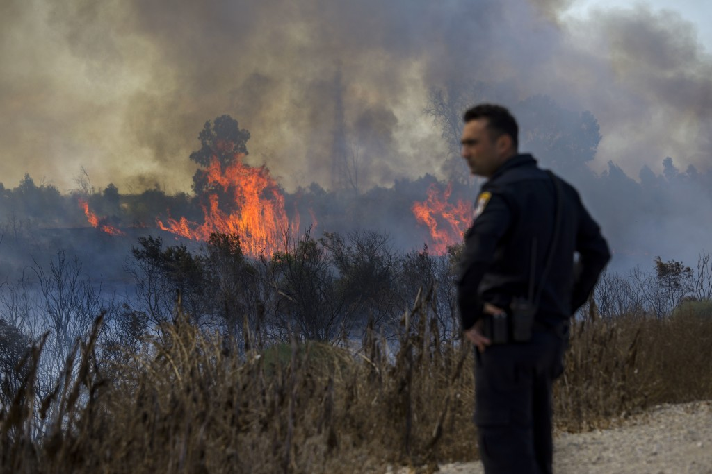 Israeli policeman watches a fire started by a balloon with attached burning cloth launched by Palestinians from Gaza Strip in Karmia nature reserve pa
