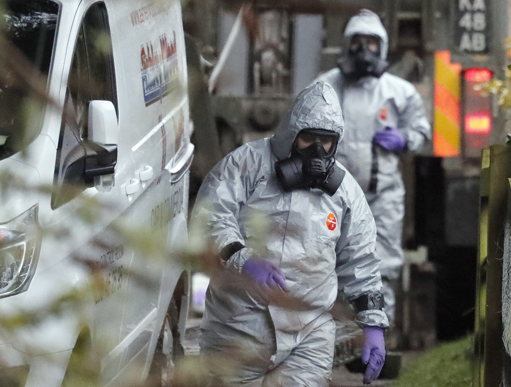 FILE - In this March 12, 2018 file photo personnel in protective gear work on a van in Winterslow, England, as investigations continue into the nerve-