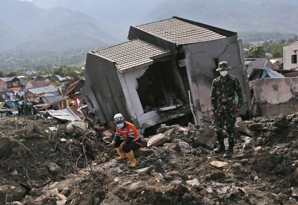 Rescuers rest near the ruin of a house at Balaroa neighborhood in Palu, Central Sulawesi, Indonesia, Thursday, Oct. 11, 2018. Indonesia's search for v