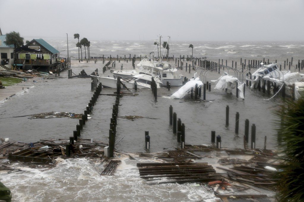 Storm Surge retreats from inland areas, foreground, where boats lay sunk and damaged at the Port St. Joe Marina, Wednesday, Oct. 10, 2018 in Port St.