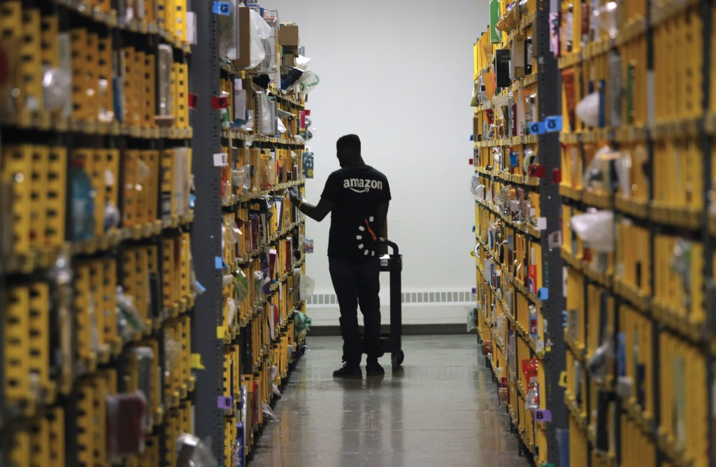 FILE- In this Dec. 21, 2016, file photo an employee of Amazon PrimeNow stacks shelves for customers making last minute holiday orders at a distributio