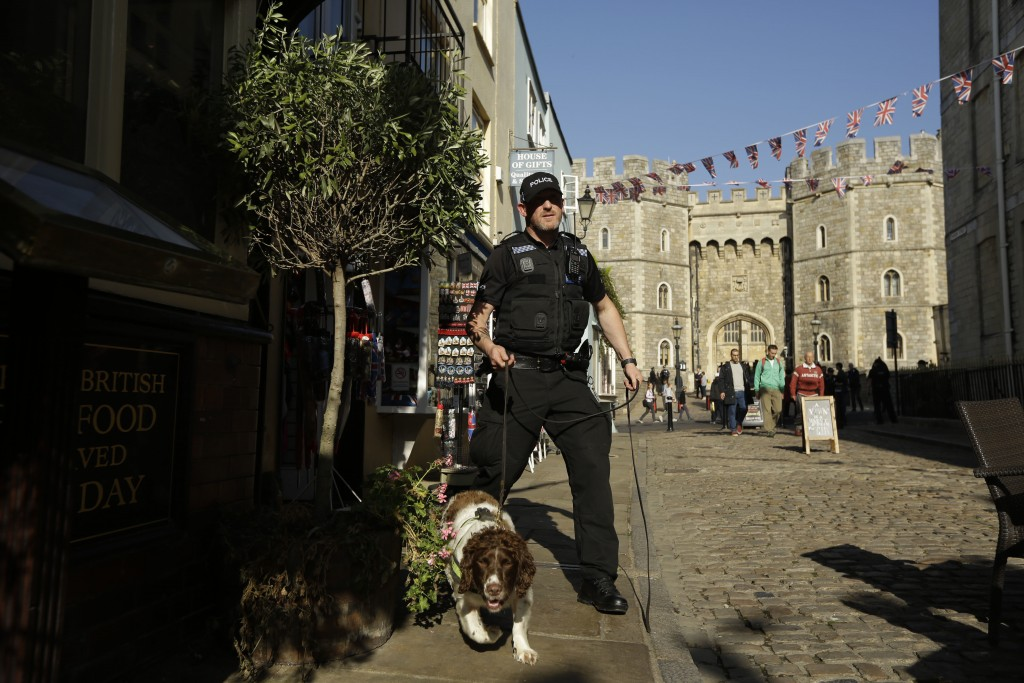 A police search dog and handler patrol outside Windsor Castle ahead of the wedding of Britain's Princess Eugenie in Windsor, England, Wednesday, Oct.