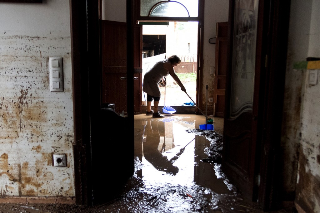 A woman clears the mud and water from her house after flooding in Sant Llorenc, 60 kilometers (40 miles) east of Mallorca's capital, Palma, Spain, Wed