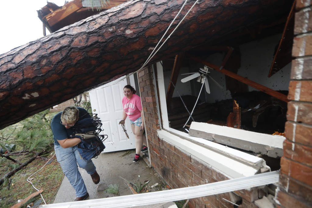 Megan Williams, left, and roommate Kaylee O'Brian take belongings from their destroyed home after several trees fell on the house during Hurricane Mic...