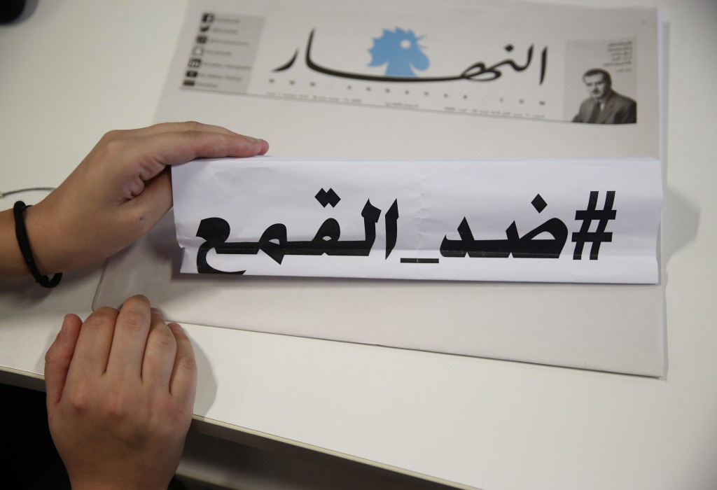 "A journalist who works at An-Nahar daily newspaper, hold a paper with Arabic words that read: ""Against the oppression,"" on a copy of a blank printed n"